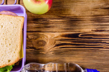 Ripe apple, bottle of water and lunch box with sandwiches on wooden table. Top view