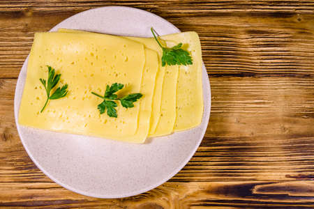 Sliced cheese and parsley in ceramic plate on rustic wooden table. Top view Stok Fotoğraf - 150621611