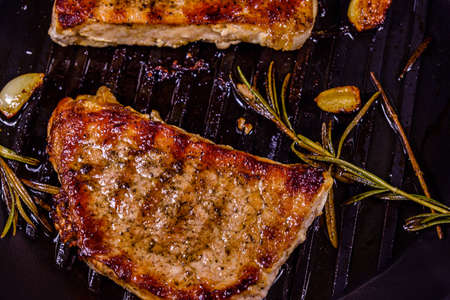 Roasted steaks with garlic, rosemary and spices in cast iron grill pan Banco de Imagens