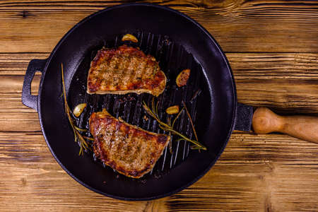 Roasted steaks with garlic, rosemary and spices in cast iron grill pan. Top view Banco de Imagens