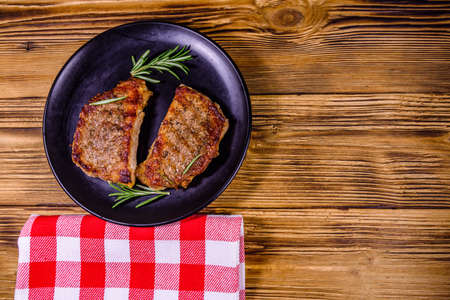 Plate with roasted steaks and rosemary twigs on wooden table. Top view Banco de Imagens