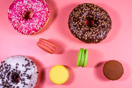 Fresh glazed donuts and french macaroons isolated on pink background Archivio Fotografico
