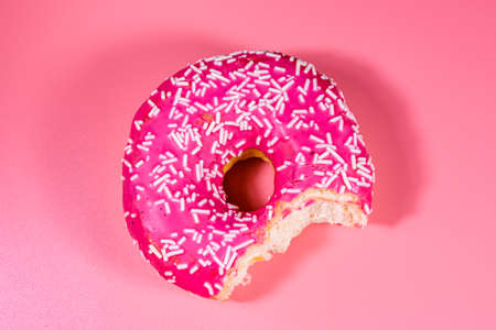 Bitten donut with glazed top isolated on pink background Archivio Fotografico