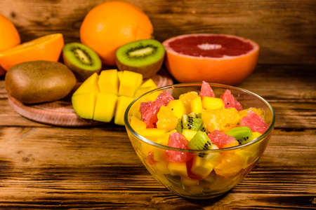 Salad with mango, oranges, grapefruit and kiwi fruits in glass bowl on wooden table Archivio Fotografico