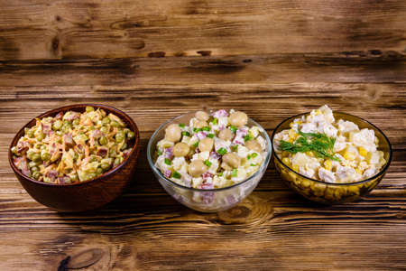 Set of festive mayonnaise salads on rustic wooden table Archivio Fotografico