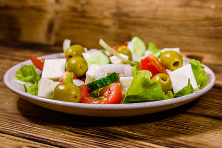 Ceramic plate with greek salad on rustic wooden table Archivio Fotografico