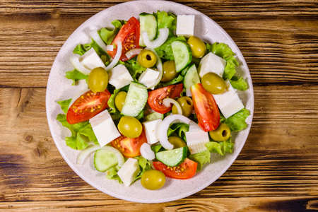 Ceramic plate with greek salad on rustic wooden table. Top view Archivio Fotografico