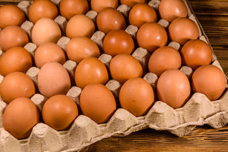 Pile of hen eggs in paper tray on wooden table