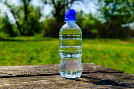 Plastic bottle with clear water on rustic wooden table Archivio Fotografico
