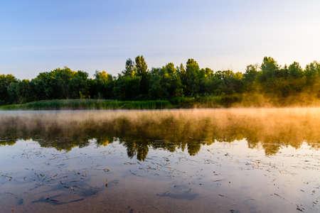 Fog above water surface. Sunrise at river Archivio Fotografico