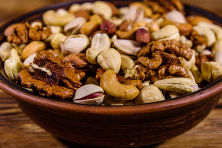 Various nuts (almond, cashew, hazelnut, pistachio, walnut) in ceramic plate on wooden table. Vegetarian meal. Healthy eating concept Archivio Fotografico