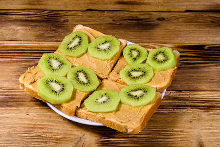 Sandwiches with peanut butter and sliced kiwi fruits in plate on wooden table Archivio Fotografico