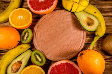 Still life with exotic fruits and cutting board. Bananas, mango, oranges, avocado, grapefruit and kiwi fruits on rustic wooden table. Top view
