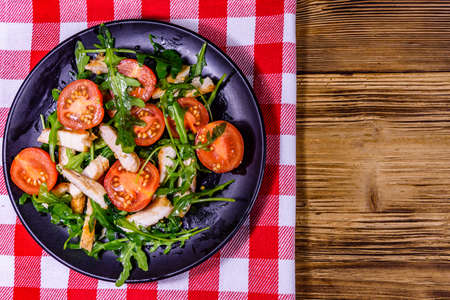 Roasted chicken breasts and salad with arugula and cherry tomatoes in ceramic plate