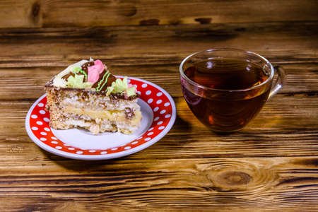 Cup of tea and plate with slice of Kiev cake with cream, nuts and meringue on wooden table