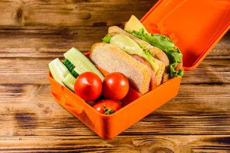 Lunch box with sandwiches, cucumbers and tomatoes on rustic wooden table