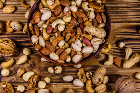 Various nuts (almond, cashew, hazelnut, pistachio, walnut) in ceramic plate on wooden table. Vegetarian meal. Healthy eating concept. Top view