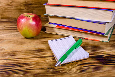 Ripe apple, opened small notepad and ball pen on a wooden table in front of stack of books Archivio Fotografico