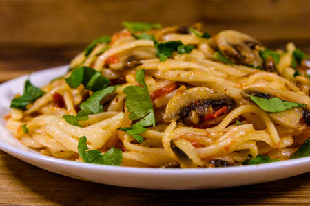 Pasta with mushrooms and tomato sauce in plate