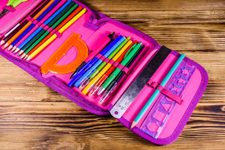 Different school stationeries (pens, pencils, ruler and protractor) in pink pencil box Archivio Fotografico