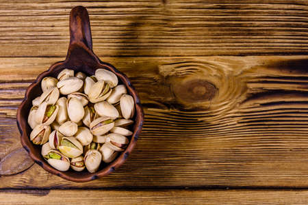 Ceramic bowl with pistachio nuts on wooden table. Top view