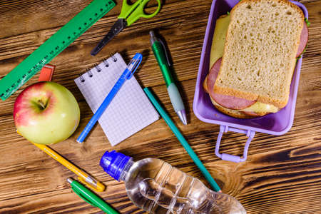 Bottle of water, ripe apple, different stationeries and lunch box with sandwiches on wooden table. Top view Archivio Fotografico