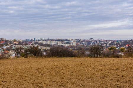 Plowed field at autumn. City Uman on background. Ukraine Archivio Fotografico