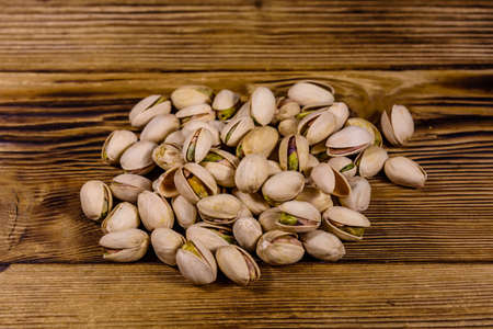 Pile of pistachio nuts on wooden table