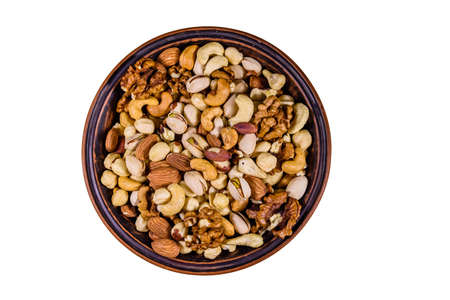Various nuts (almond, cashew, hazelnut, pistachio, walnut) in ceramic plate isolated on white background. Vegetarian meal. Healthy eating concept Archivio Fotografico