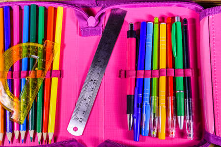 Different school stationeries (pens, pencils, ruler and protractor) in pink pencil box. Top view Archivio Fotografico