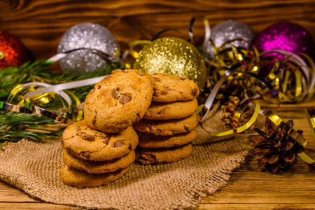 Stack of chocolate chip cookies on sackcloth in front of christmas decorations Фото со стока