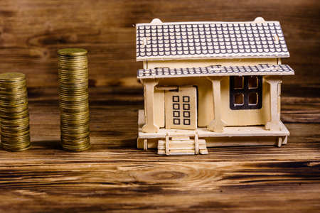 Plywood model of house and stacks of coins on wooden background Stock fotó