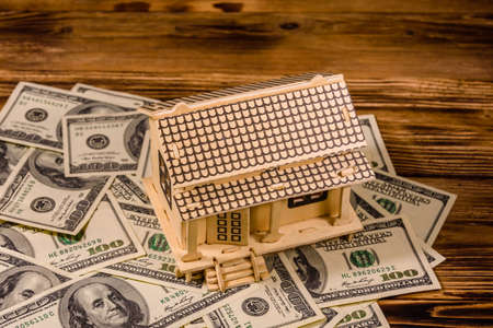 Plywood model of house and one hundred dollar banknotes. Loan, real estate concept