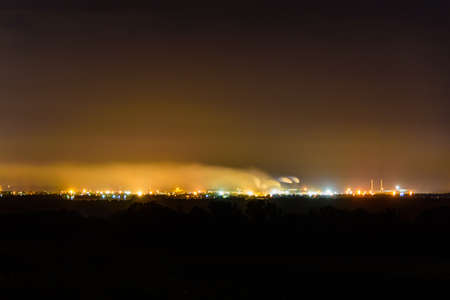 View on city lights at night. Smoke from chimneys of factory rises to sky. Environmental pollution concept