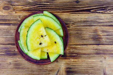 Plate with sliced yellow watermelon on wooden table. Top view 写真素材