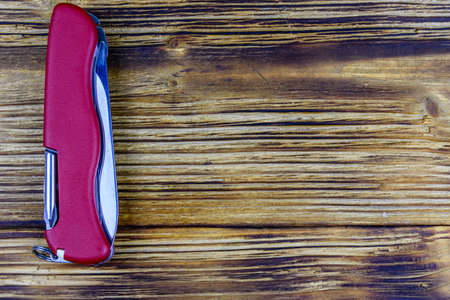 Folded all purpose red pocket knife on a wooden background