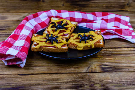 Sandwiches with spider and spider web on wooden table. Halloween celebration concept