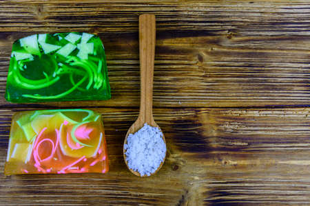 Pieces of handmade soap and spoon with sea salt on wooden background. Top view 写真素材