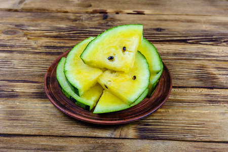 Plate with sliced yellow watermelon on wooden table