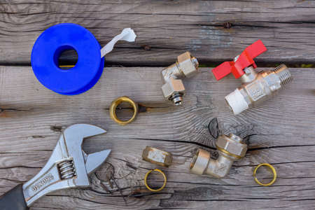 Different plumbing spare parts, sealing tape and adjustable wrench on wooden background. Top view 写真素材