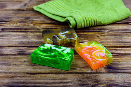 Pieces of handmade soap and towel on wooden background