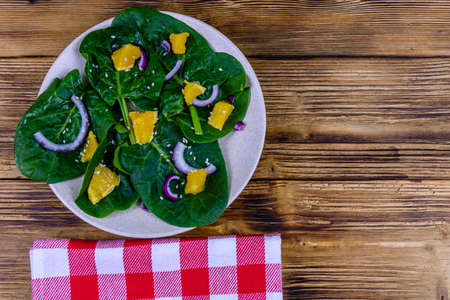 Salad with spinach leaves, pieces of orange, sesame seeds and onion in ceramic plate. Top view