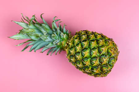 Whole ripe pineapple on a pink background