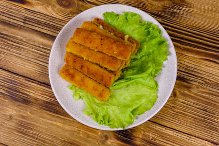 Baked fish sticks and lettuce leaves in plate. Top view 写真素材