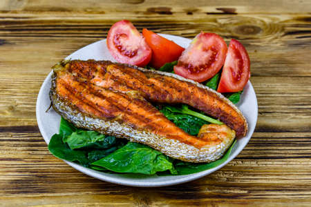 Plate with roasted salmon steak, tomatoes and spinach leaves on wooden table