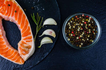 Raw salmon steak and spices on slate board. Top view