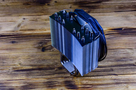 Modern cpu cooler with heat pipes on wooden background