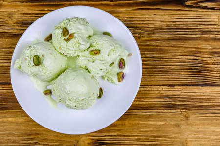 Glass bowl with pistachio ice cream balls and nuts on wooden table. Top view