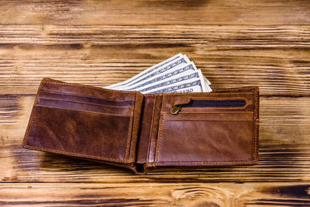 Brown leather wallet and one hundred dollar banknotes on wooden background