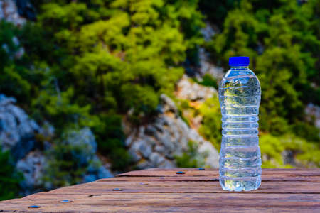 Bottle of water on wooden table. Deep canyon on background